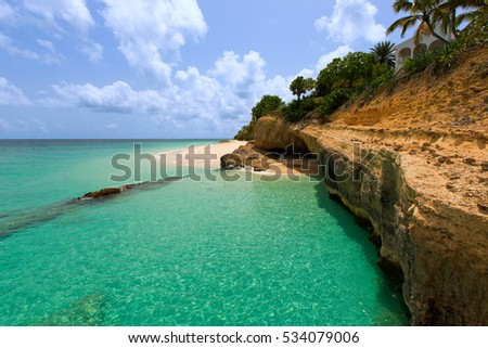 view of rugged rocky coast at anguilla island, caribbean, with turquoise water and white sand beach