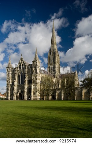 View of Salisbury Cathedral in England with blue sky and white clouds - stock photo