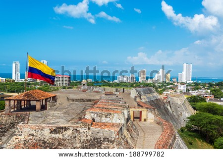 View of San Felipe de Barajas castle and the skyline of Cartagena, Colombia with a large Colombia flag - stock photo