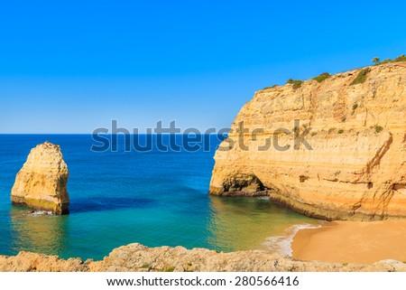 View of sandy beach and rock cliffs near Carvoeiro town, Algarve, Portugal - stock photo