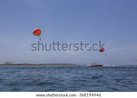 View of scenic Bali Beach with sky parachute as a main subject.  - stock photo