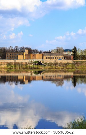 View of scenic river coastline with buildings, on cloudy blue sky background. - stock photo