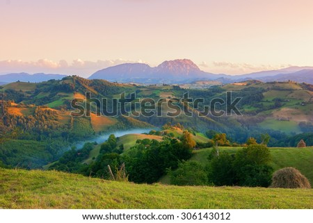 View of scenic valley with mountain range in the background at sunset - stock photo