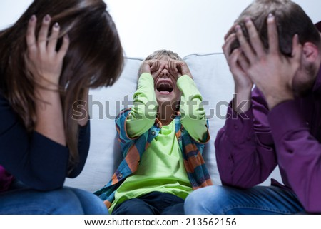 View of screaming boy and tired parents - stock photo