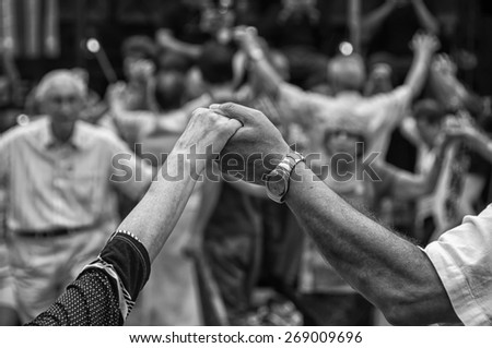 View of senior people holding hands and dancing national dance Sardana at Plaza Nova, Barcelona, Spain. It is a type of circle dance typical of Catalonia - stock photo