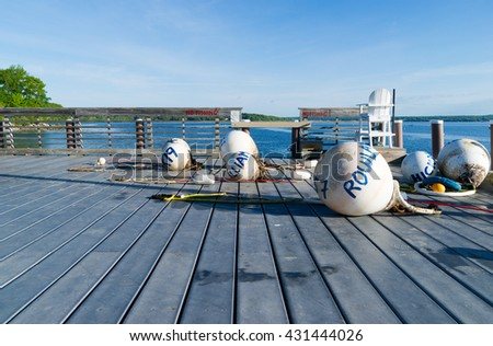 View of several buoys ready to be placed at their moorings on a metal deck at Northport Maine in the early morning light. - stock photo