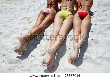 View of several feminine bottoms sunbathing on the beach - stock photo