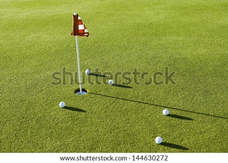 View of several golf balls by flag on golf course