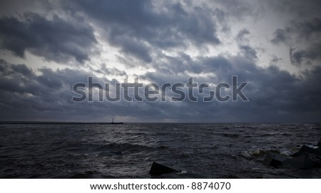 View of sky and sea few minutes before storm. Lighthouse at horizon. - stock photo
