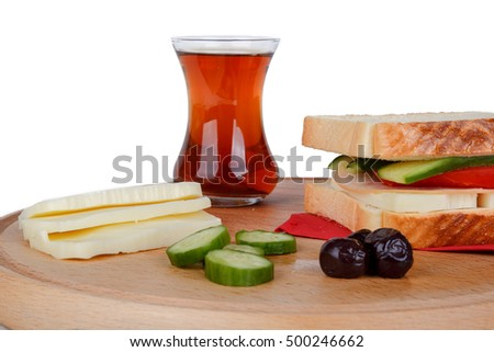 View of slice of bread with black tea, cheese, olive and cucumber around, isolated on white background.