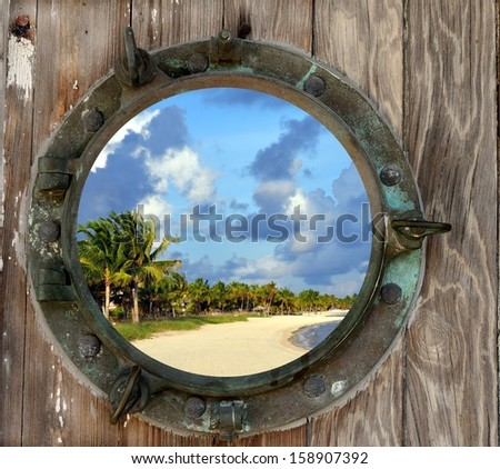 View of Smathers Beach in Key West, Florida, through a old, rustic porthole. - stock photo