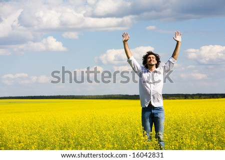 View of smiling man raising his hands standing in the field - stock photo