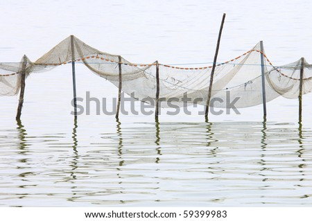 view of some fishing nets on standing water - stock photo
