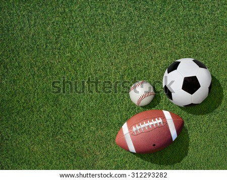 View  of sports equipment including baseball, soccer and football on grass background. - stock photo