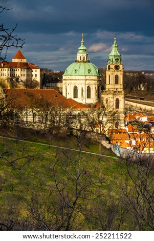 View of St. Nicholas Church with Green Park and Cloudy Sky - Prague, Czech Republic - stock photo