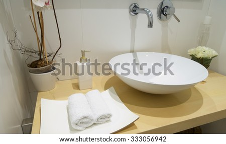 view of stacked towels and soap in a modern toilet