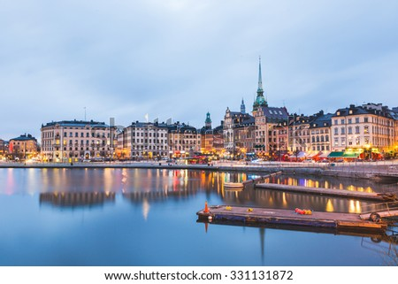 View of Stockholm old town at dusk. Long exposure shot, with water on foreground and blurred clouds on the sky. Typical scandinavian architecture and colors. Travel and tourism concept. - stock photo