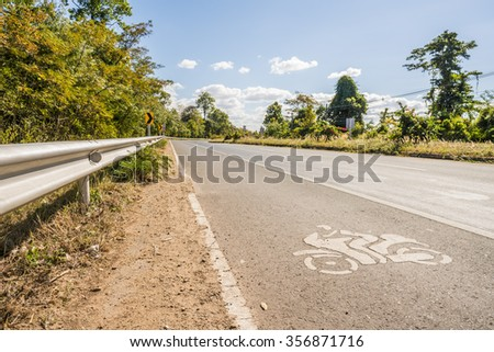 view of suburban asphalt road and motorcycle sign on the road - day time Large curving highway in rural area on cloudy sky. - stock photo