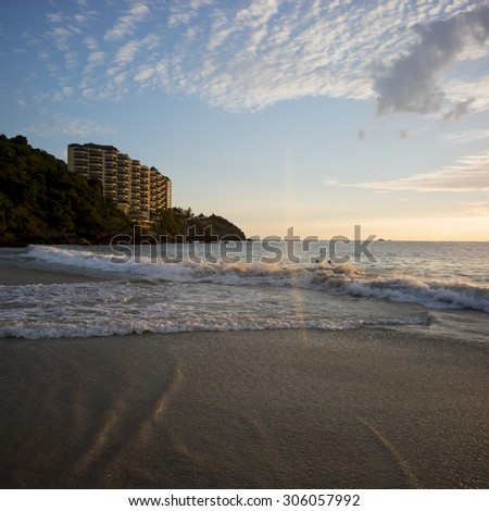 View of surf on the beach at sunsest with apartment buildings in background, Ixtapa, Zihuatanejo, Guerrero, Mexico - stock photo