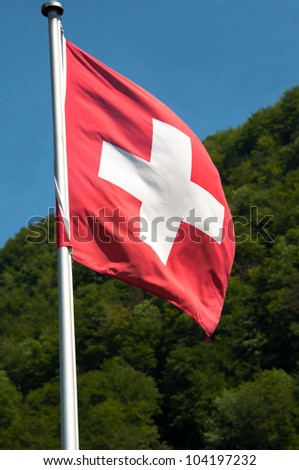 View of Switzerland countryside - swiss flag with green mountains in the background - stock photo
