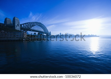 View of Sydney Harbour with Sydney Harbour bridge and distant skyline at dusk in Sydney, Australia.