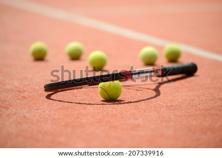 View of tennis racket and balls on the clay tennis court - stock photo
