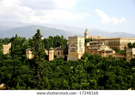 View of the Alhambra palace in the late afternoon Sun with the Sierra Nevada mountains in the background - stock photo