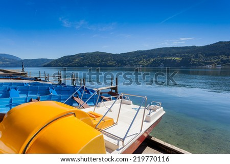 View of the alpine lake of Millstatt with paddle boats. Millstatt am See, Carinthia, Austria - stock photo
