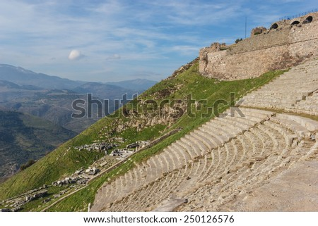 view of the amphitheater and the ruins of the temple of Dionysus on the lower slopes of the amphitheater - stock photo