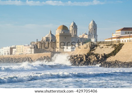 View of the Ancient Cadiz Cathedral. The waves on the winter Atlantic Ocean. Spain - stock photo