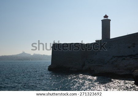 """View of the ancient lighthouse on the island """"Chateau dIf"""" and Marseille in South France against the morning sun - stock photo"""