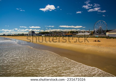 View of the beach and rides from the pier at Old Orchard Beach, Maine. - stock photo