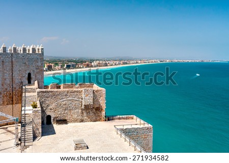 View of the beach at Valencia and the castle of Peniscola. Spain. Beautiful coastline with beaches, hotels and turquoise sea. Part of the old fortress. Clear sunny day, cloudless sky. - stock photo