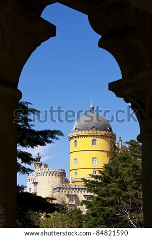 View of the beautiful of Pena palace seen through an arch from the garden in Sintra, Portugal