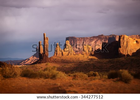 View of the beautiful red-orange rocks in light of the white-purple sunset in Monument Valley. Navajo Reservation in Arizona, USA.