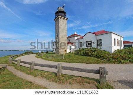 View of the Beavertail Light lighthouse near Jamestown on Conanicut Island, Rhode Island, with a bright blue sky and white clouds - stock photo