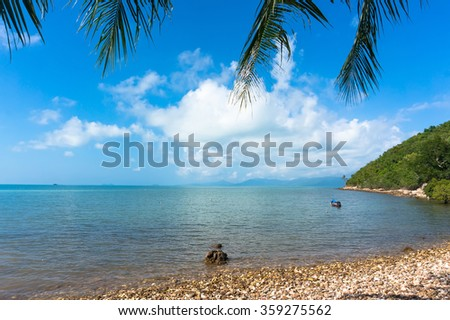 View of the blue sea under palm trees on the beach. Koh Samui Thailand