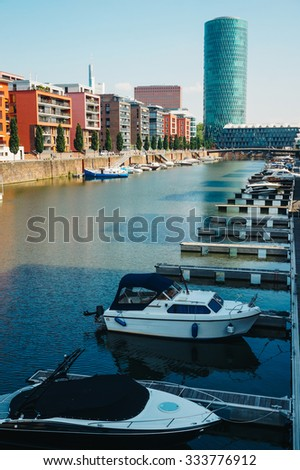 View of the boats anchored on Main's shore, residential buildings and Westhafen tower in Frankfurt, Germany