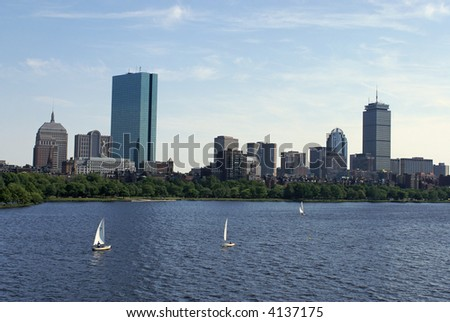 View of the boston skyline from across the charles river, the water is choppy and there are sailboats in the water
