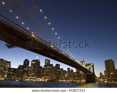 View of the Brooklyn bridge and south Manhattan from Brooklyn at dusk. - stock photo