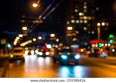 View of the city at night after the rain, the car driving on the road - stock photo