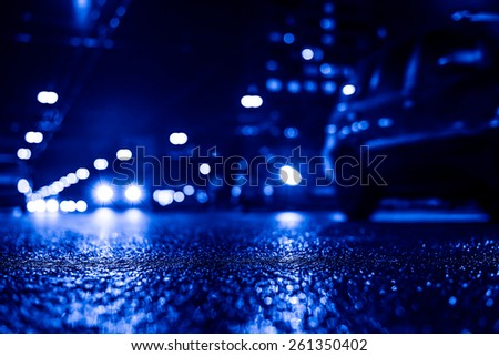 View of the city at night after the rain, the cars driving on the road and shine the headlights. View from the level of asphalt level, Image in the blue toning - stock photo
