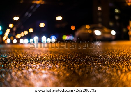 View of the city at night after the rain, the cars driving on the road and shine the headlights. View from the level of asphalt level - stock photo