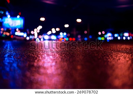View of the city at night after the rain, the cars driving on the road and shine the headlights. View from the level of asphalt level, image in the blue-purple toning - stock photo