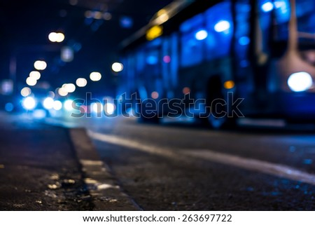 View of the city at night, the bus driving on the road. View from the curb at the asphalt level, in blue tones - stock photo