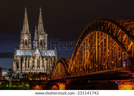 View of the Cologne Cathedral and Hohenzollern Bridge across the Rhine, Germany, at dusk - stock photo