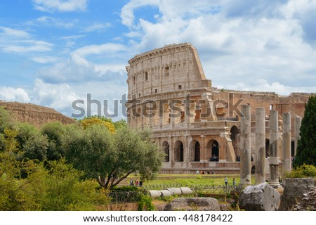 view of the Colosseum after restoration from the forum through the trees in Rome Italy