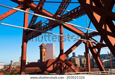 View of the downtown Portland with high-rise buildings, the train station tower clock, through the metal farm vehicle bridge, part of which is illuminated by the sun, with the power line for the tram. - stock photo