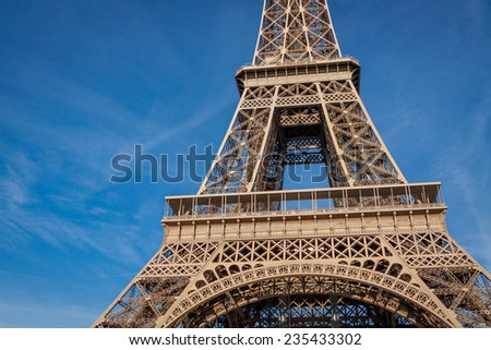 View of the Eiffel Tower in Paris on the Champs de Mars against a blue sky, one of the most visited and iconic landmarks in France with its distinctive wrought iron lattice frame - stock photo