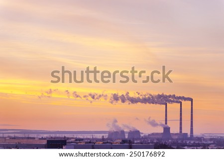 View of the factory with smoking chimneys - stock photo